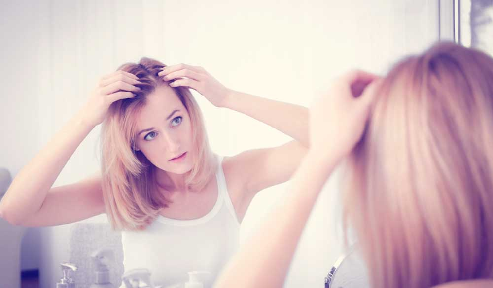 Woman checking for hair loss in the mirror